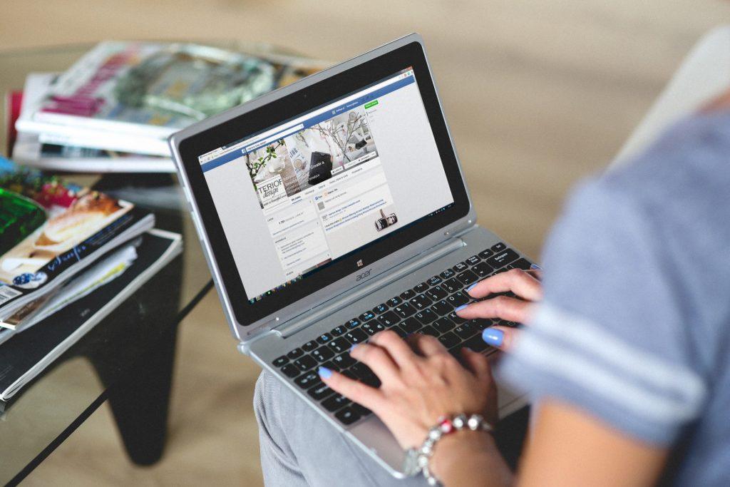 Mujer viendo Facebook en su computadora